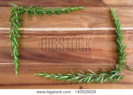 Sprigs of rosemary on a wood cutting board