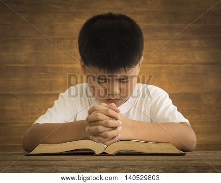 The boy put his hand on the Bible pray to God.