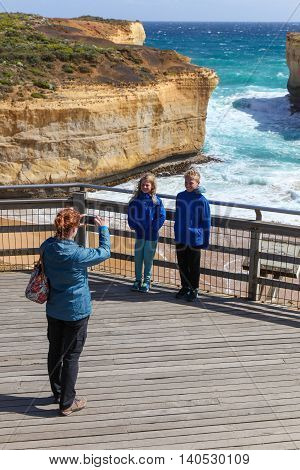 A woman takes a photo of her children at London Bridge rock formation on the Great Ocean Road - Victoria Australia. The coastline along the Great Ocean road is a famous tourist destination.