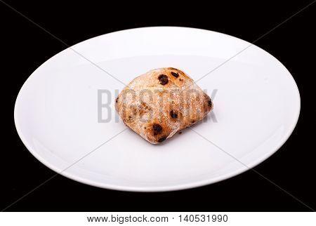 Sandwich bun with raisons on white plate