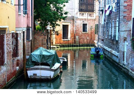 A typical small street in Venice with two boats docked and drying clothes