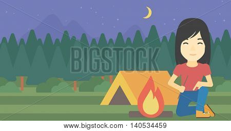 An asian woman kindling campfire on the background of camping site with tent. Tourist relaxing near campfire. Woman sitting near campfire. Vector flat design illustration. Horizontal layout.
