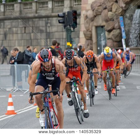STOCKHOLM SWEDEN - JUL 02 2016: Group of colorful male triathlete cyclists Adam Bowden in the lead competitors behind in the Men's ITU World Triathlon series event July 02 2016 in Stockholm Sweden