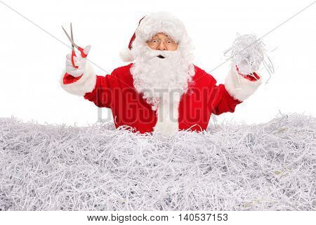 Studio shot of Santa Claus cutting paper with scissors and standing in a pile of shredded paper isolated on white background