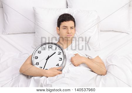 Frustrated young man lying in bed and holding a clock in his hand isolated on white background