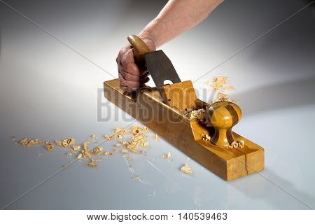 Hand of an old man holding old wooden planer with wood chips on the foreground and background.