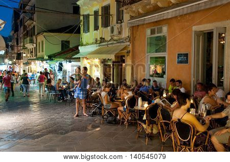 CORFU-AUGUST 25: Tourists have dinner in a local restaurant on August 25 2014 in Kerkyra town on the Corfu island Greece.