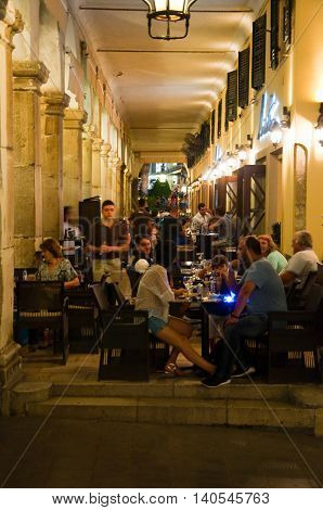 CORFU-AUGUST 25: Tourists have dinner in a local restaurant on the Liston of Corfu on August 25 2014 in Kerkyra town on the Corfu island Greece.
