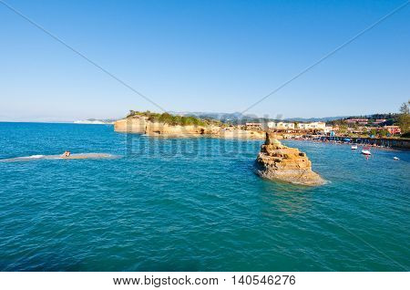 Famous Sidary beach holidaymakers sunbath on the a sandy shore. Corfu Greece.