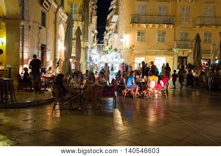 CORFU-AUGUST 25: Tourists have dinner in a local restaurant at night on August 25 2014 in Kerkyra town on the Corfu island Greece.