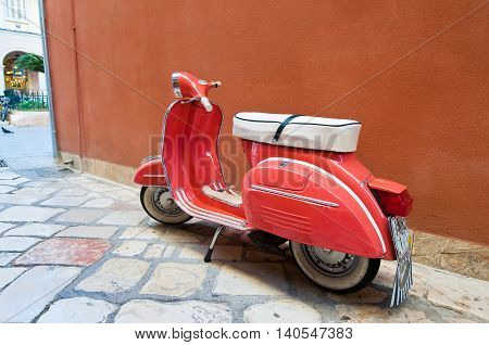 CORFU-AUGUST 22: Vintage Vespa scooter on Kerkyra street on August 22 2014 on Corfu island in Greece. Vespa is an Italian brand of scooter manufactured by Piaggio.