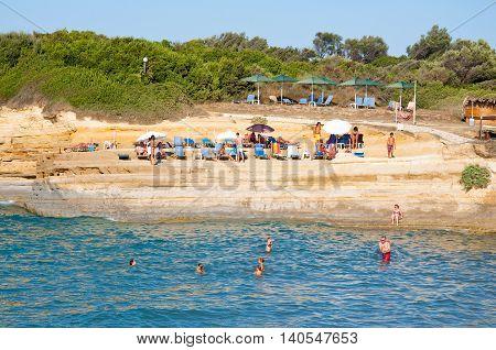 CORFU-AUGUST 26: Sidary beach people sunbath on the sandy shore on August 262014 on Corfu island Greece.