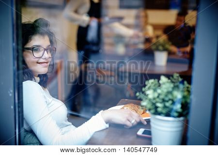 Young woman sitting in cafe, smiling. Photographed from outside.