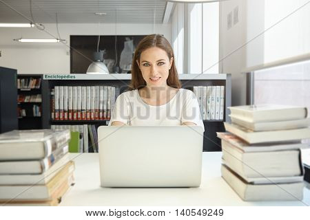 Portrait Of Beautiful Happy Young Female Student With Long Hair Sitting In The Library In Front Of L
