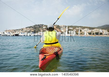 Backview Shot Of Young Tourist Paddling On Kayaking On Blue Sea In Sunny Day. Awesome And Beautiful