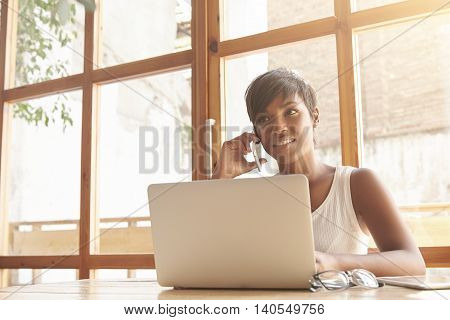 Young Dark-skinned Female Boss Talking On Phone With Partners. Attractive Woman With Short Hair And