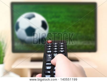 Man watching football game on tv at home.