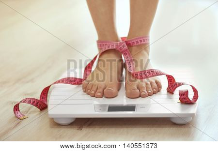 Female legs standing on floor scales with centimeter