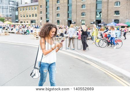 Young Woman Playing With Augmented Reality Game In London