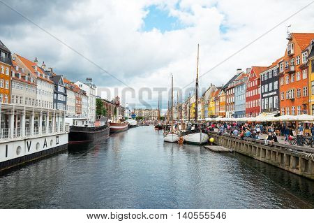 Copenhagen Denmark - July 20 2015: A crowd of tourists betveen the raditional houses and boats in the Nythavn canal