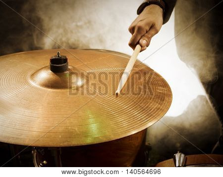 Drummer hitting sticks in ride. The dark background in the smoke.