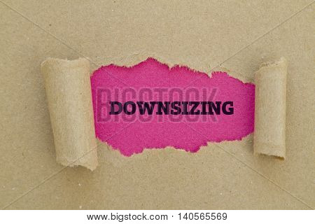 DOWNSIZING word written under torn paper .