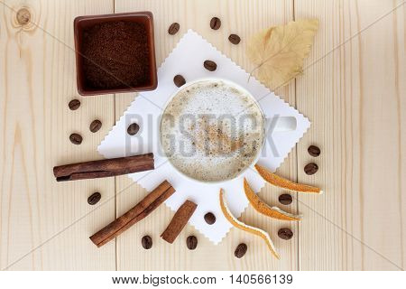 frothy coffee with cinnamon sticks and orange peels in a white mug top view / flavors of coffee