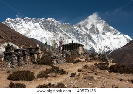 Mani wall and prayer flags along the trail to to Pangboche with summit of Mt. Everest above Nuptse to Lhotse ridge in the background Pangboche Solukhumbu Nepal.