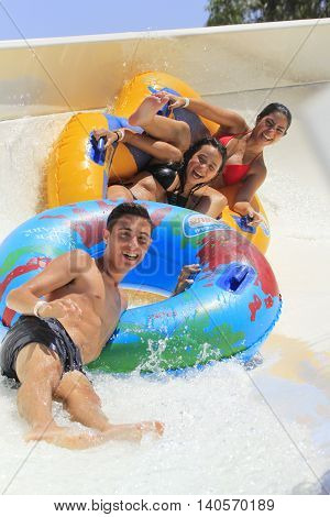 Rhodes Greece-July 26 2016:Two cheerful girls and boy drive with tube on the rafting slide in the Water park.Rafting slide is one of many popular game for adults and children in park.Water Water Park is located on the island of Rhodes in Greece
