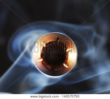 Hollow point bullet aimed at the camera with smoke behind