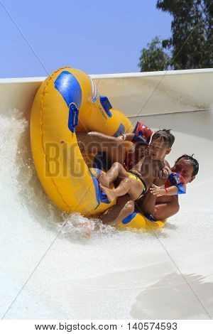 Rhodes Greece-July 26 2016:Father and sun drive with tube on the rafting slide drive with tube on the rafting slide in the Water park.Rafting slide is one of many popular game for adults and children in park.Water Park is located on the Rhodes in Greece