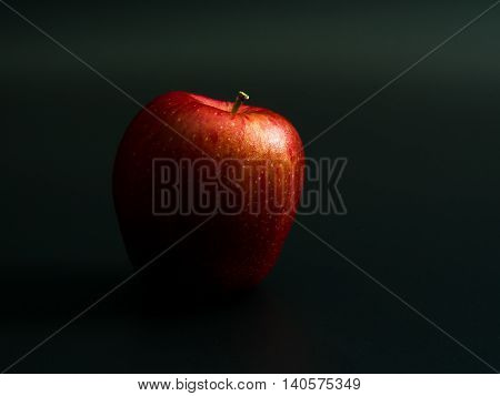 Red Apple on a black background .The light from the right of the image
