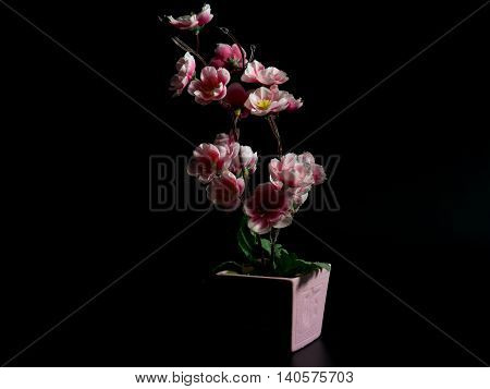 Artificial Flowers on a black background .The light from the right of the image.