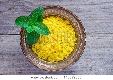 Top view of an antique metal bowl with cooked turmeric jasmine rice with mint leaves