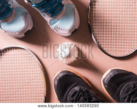 sports set of black orange sport shoes and blue sport shoe and shuttlecocks with two badminton racket on sport background in concept family activity