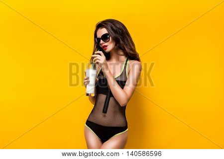 Portrait of sexy brunette in black beachwear and sunglasses drinking cocktail. Isolated.