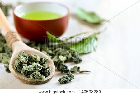 Wooden spoon with dried green tea leaves in it and a cup of green tea on a backstage