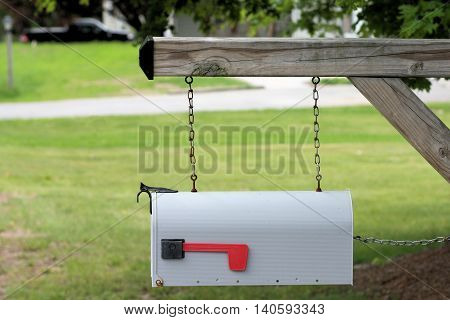 Rural mailbox hanging on steel chains to prevent vandals from knocking it off its base.