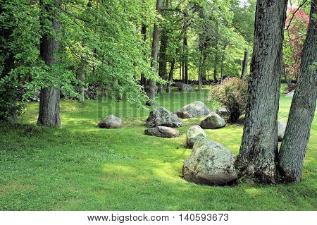 Large boulders scattered about on a green lawn.