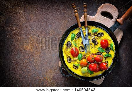 Frittata or omelet with mushrooms and tomatoes in a pan mediterranian course top view