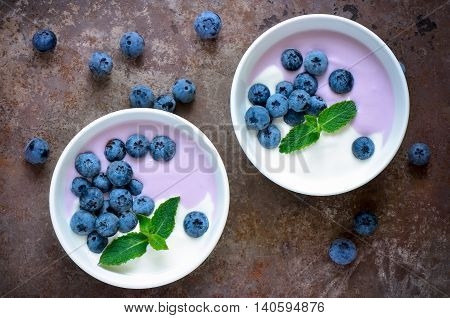 Light greek yogurt or cream dessert with fresh blueberries served in two white bowls; top view; stylized photo