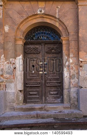 Door of an abandoned house from a year 1899 with 4 padlocks. Old facade and stairs. Medieval city Banska Stiavnica Europe.