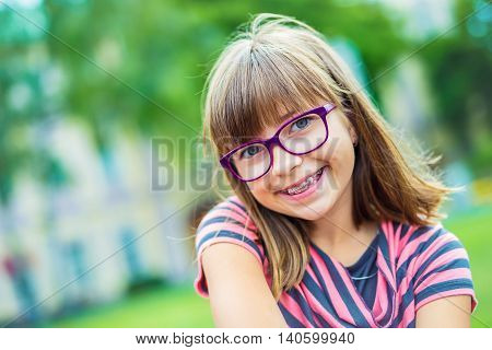 Girl. Teen. Pre teen. Girl with glasses. Girl with teeth braces. Young cute caucasian blond girl wearing teeth braces and glasses.