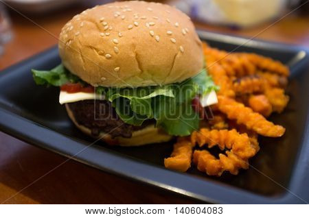 Cheeseburger on a whole wheat bun with crinkle cut sweet potato fries