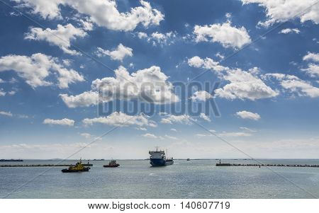 Cargo Ship and Tugboat. Seascape with beautiful sky. Stock photo
