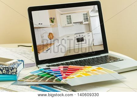 designer's working table - open notebook with refubrished kitchen and colour charts