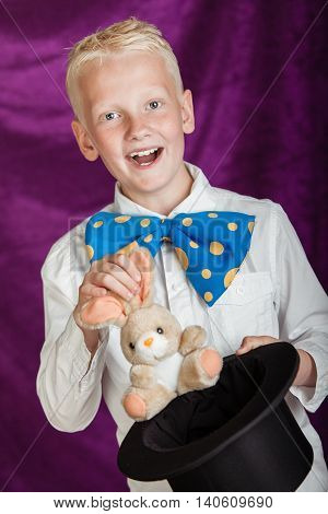 Fun Young Magician Pulling A Bunny From A Top Hat