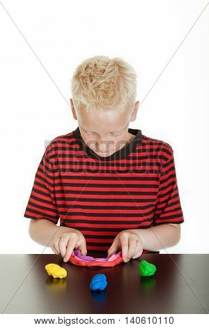 Creative Young Boy Playing With Plastic Putty