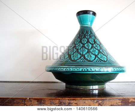 Green and black Moroccan tagine (cooking vessel) on a table