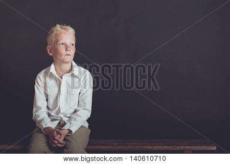 Lonely Boy Looking Upward While Sitting On Bench